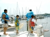 7/18/07: (L-R): Eris Lewis-Carrol, 11, Miguel Gonzalez, 9, teacher Gray Williams, and Michael McFarland, 7, cast fishing lines before getting ready to head out on the boat. Photo By: Anna Tolner