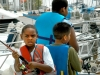 7/18/07: (L-R): Michael McFarland, 7, Eris Lewis-Carrol, 11, and Miguel Gonzalez, 9, cast fishing lines before getting ready to head out on the boat. Photo By: Anna Tolner